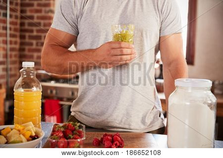 Man holding holding homemade smoothie, mid section