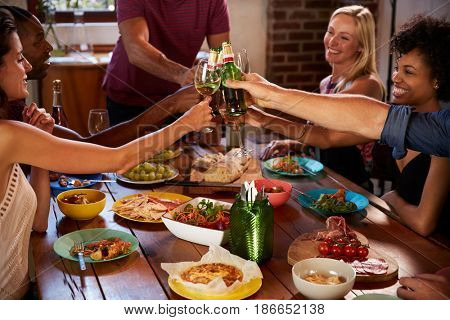Host and friends making a toast at a dinner party, close up