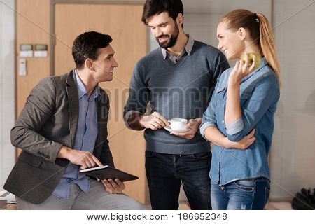 Do you agree. Attractive man sitting on the table in semi position holding tablet in both hands while looking at his partners
