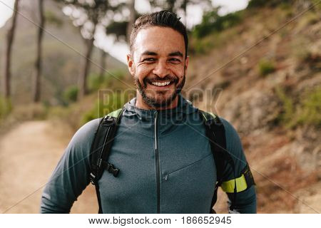 Portrait of healthy young caucasian man standing outdoors and smiling. Confident young male runner on country road.