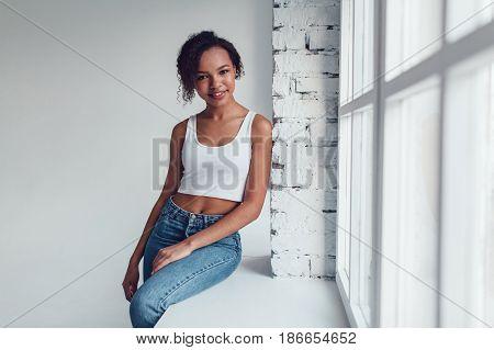 Beautiful african girl in white tops sitting on a windowsill.