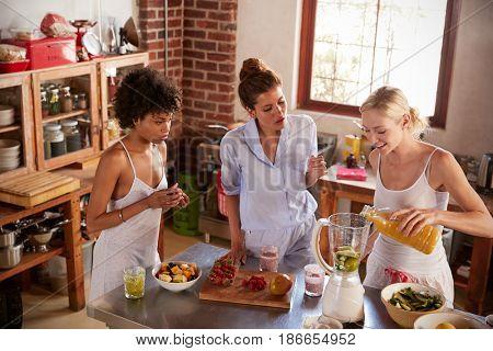 Three female friends making smoothies in kitchen