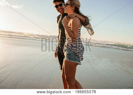 Romantic Young Couple Strolling On The Beach