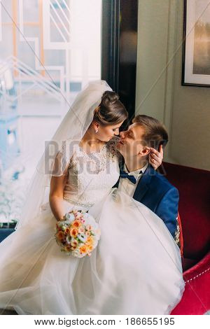 Charming young bride holding wedding bouquet sitting on knees of her loving groom in a luxurious chair with shiny windows as background. Close up.