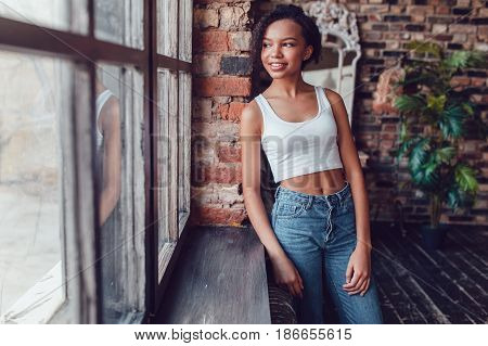 Beautiful african girl in white top standing near the window.