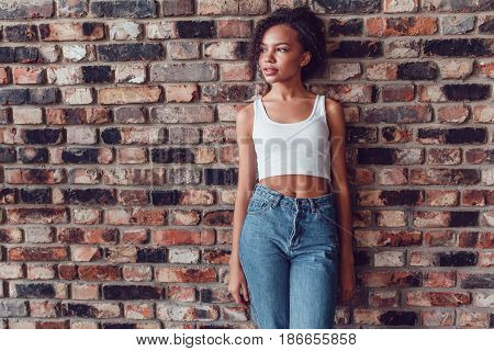 Beautiful african girl in white top standing on a brick wall background.