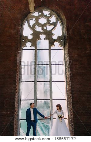 Just married posing in front of old gothic cathedral arched window decorated with tracery.