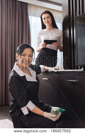 Pleasant job. Cheerful happy nice hotel maid sitting on the floor and doing the cleaning while being happy about her job
