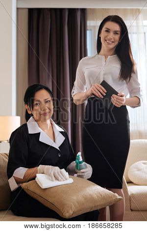 Hotel manager. Joyful attractive beautiful woman standing near the hotel maid and holding a tablet while being in a good mood