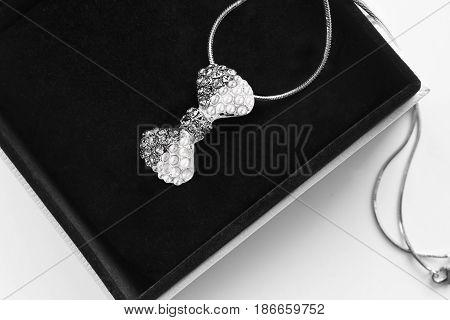 Diamonds and pearl bow shaped pendant in jewel box closeup