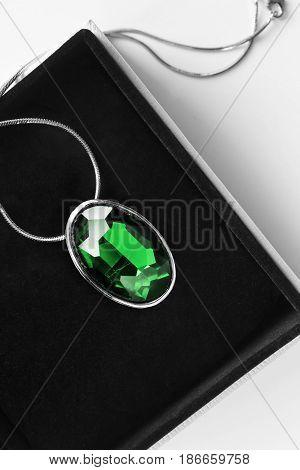 Vintage large emerald medallion in black jewel box closeup