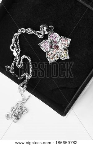 Silver flower pendant with pink crystals in black jewel box