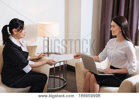 I am hired. Delighted nice pleasant hotel maid sitting opposite the manager and taking an employment contract while being taken on