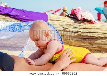 Baby On Woman Stomach On Beach