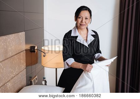 Daily routine. Pleasant nice Asian hotel maid holding a sheet and looking at you while cleaning the bed