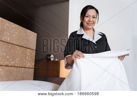 Hotel maid. Pleasant nice positive woman holding a sheet and smiling while being in a good mood