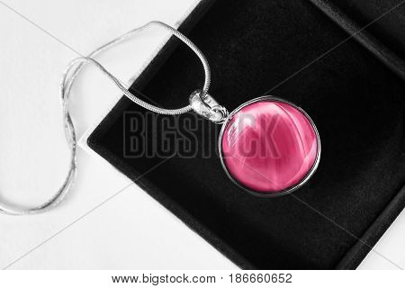Pink glass medallion on silver chain in black jewel box closeup