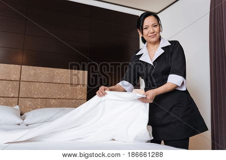 Service in the hotel. Good looking nice positive hotel maid holding a sheet and smiling while changing bedding