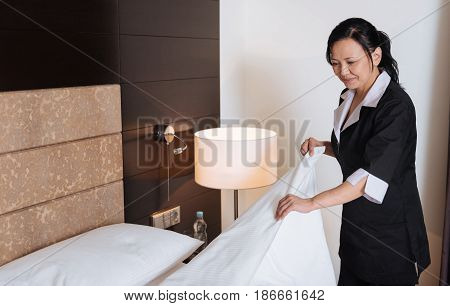 Change of bed linen. Hard working professional Asian hotel maid smiling and changing the bed linen while doing her duties
