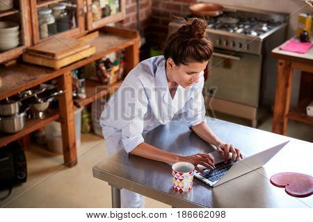 Woman in pyjamas stands using laptop in kitchen, high angle