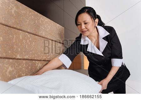 Hotel bedding. Nice pleasant hard working woman putting a pillow in the right place and smiling while working in the hotel room