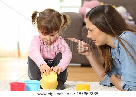 Portrait of a mother scolding to her baby daughter sitting on the floor in the living room at home