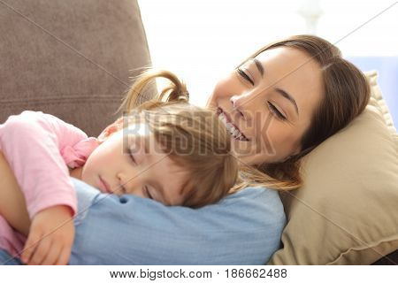 Close up of a proud mother watching her baby sleeping lying on a sofa in the living room at home