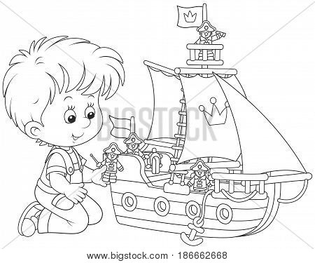 Little boy playing a toy sailing ship