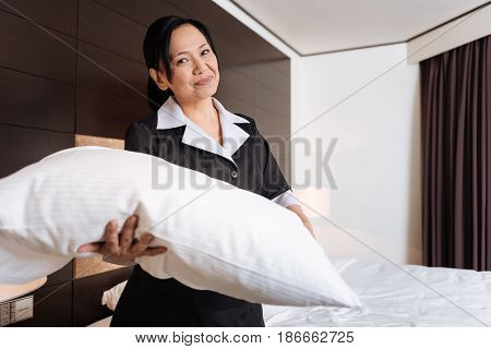 Hotel room. Joyful good looking hotel maid standing in the hotel room and smiling while changing the bedding