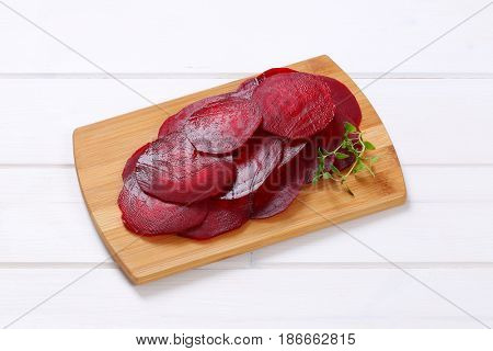 stack of thin beetroot slices on wooden cutting board