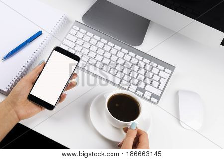 Woman hands holding the phone with isolated screen and cup of coffee. Business workplace with keyboard and business objects