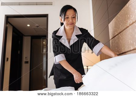 In the hotel room. Hard working professional delighted hotel maid leaning over the bed and arranging the pillow while being in a positive mood