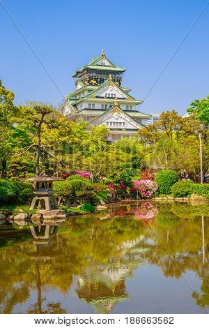 Spectacular Osaka Castle reflecting in a pond in Osaka Castle Park, the most popular hanami spot during cherry blossom. Osaka Castle is one of most famous landmarks of Japan and Osaka. Vertical shot.