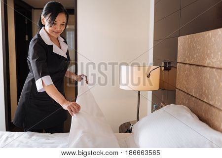 Change of bedding. Positive nice joyful hotel maid standing near the bed and looking at it while changing the bed clothing