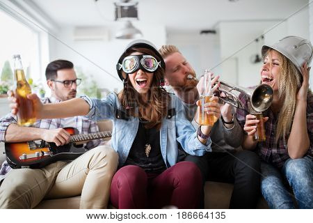 Happy group of young friends having fun and partying to music