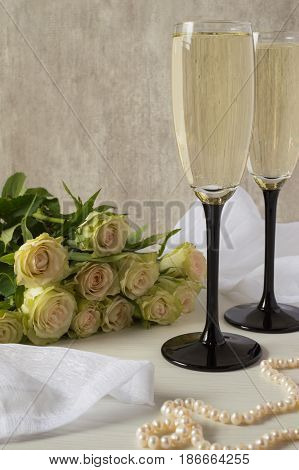 A bouquet of white roses, two glasses of champagne and pearl necklace.
