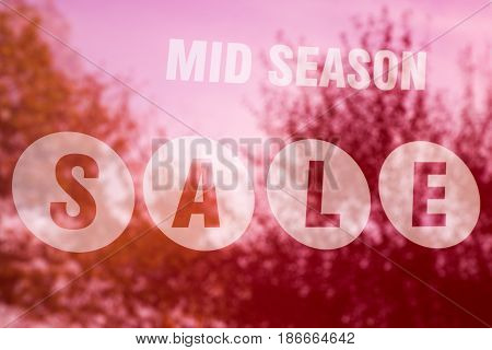 Mid Season Sale sign in a store window with the colorful magenta hued reflection of shrubs and trees in a close up view on the glass in a shopping and discount concept