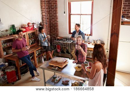 Five friends stand hanging out in kitchen, elevated view