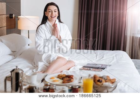 So delicious. Delighted happy beautiful woman sitting on the bed and clapping her hands while looking at the table with food