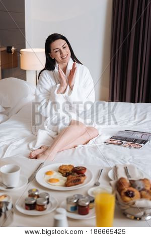 It looks so great. Happy cheerful pretty woman looking at the table with food and clapping hands while sitting on her bed in the hotel room