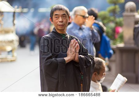 TAIPEI, TAIWAN - MARCH 28, 2017 : A man is praying at the Lungshan Buddhist temple during a ceremony in Taipei, Taiwan