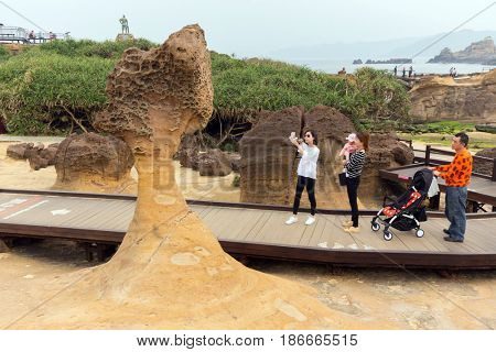 YEHLIU, TAIWAN - MARCH 30, 2017 : Some tourists are photographing an amazing geologic natural sandstone formation at the Yehliu geopark, Taiwan