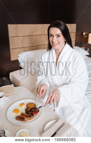 Eating breakfast. Happy positive young woman sitting at the table and holding a knife and fork while eating her breakfast