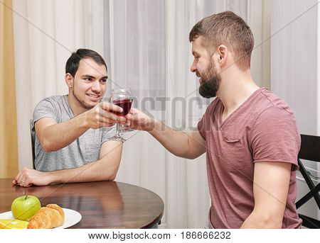 Happy gay couple drinking wine in kitchen