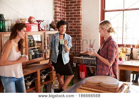 Three young adult girlfriends talk over coffee in kitchen