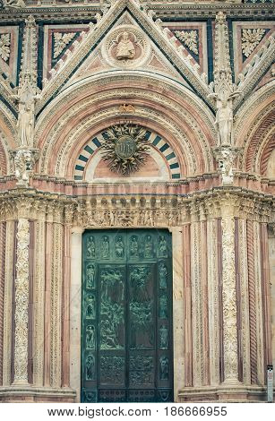 Ornate green door on a Cathedral in Siena Italy