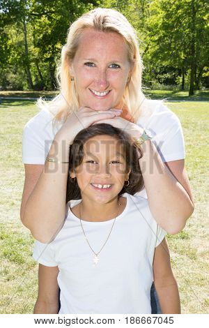 Blonde Mother With Her Brown Daughter In Garden Park