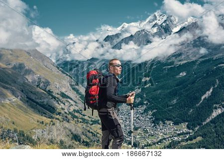 hiker on the trail in the Apls mountains. Trek near Matterhorn mount. Mountain ridge and Zermatt town on the background
