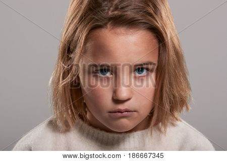 Sad nine year old girl looking to camera, head and shoulders