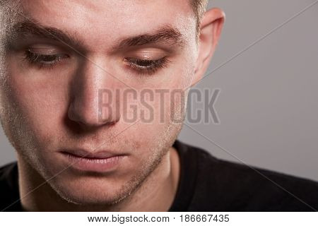 Young white man looking down, close up